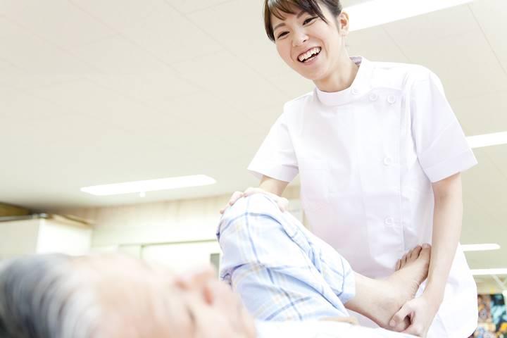 女性理学療法士が患者さんの下肢可動域訓練をしている画像