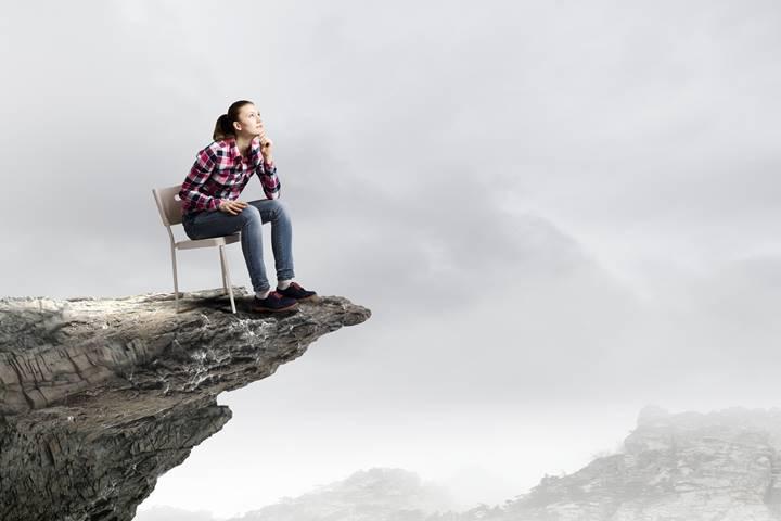 女性理学療法士が石の上で座って考え込んでいる画像