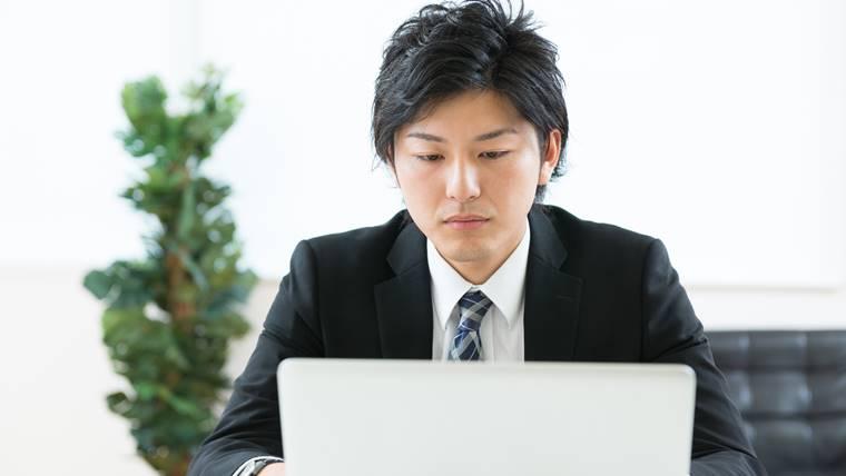 男性理学療法士が転職先をパソコンで探している画像