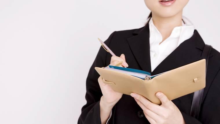 女性理学療法士がリクルートスーツ着て何かをメモしてる画像