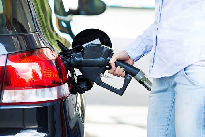 女性理学療法士が車にガソリンを入れている画像