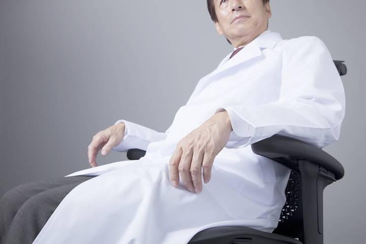 病院の院長が白衣を着て座っている画像