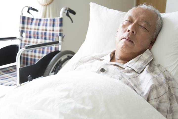 訪問リハビリで患者さんがベッドに寝てる写真