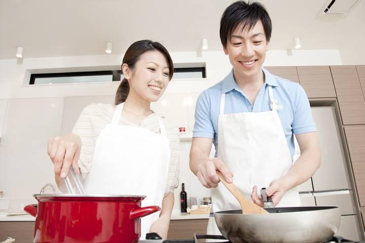 男性理学療法士がキッチンで食事を作っている画像