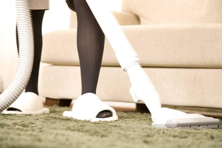 掃除機をかけている女性理学療法士の脚の画像