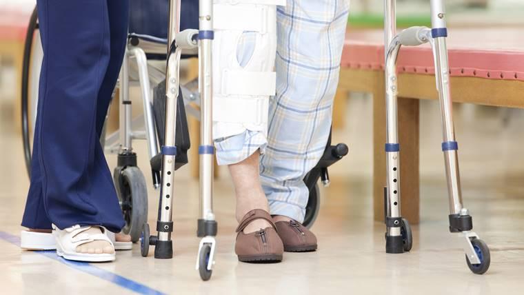 理学療法士が歩行器歩行の患者さんを介助している画像